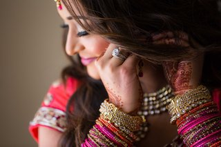 bride-puts-on-earrings-while-wearing-stacked-pink-red-orange-bangle-bracelets-and-henna-on-hands