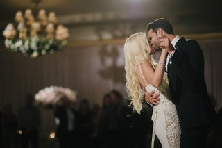groom-in-black-tuxedo-kisses-bride-in-galia-lahav-gown-with-lace-panels-during-first-dance