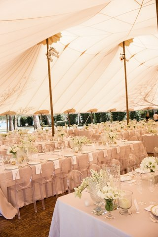 tent-wedding-reception-with-long-tables-tan-linens-white-napkins-flowers-clear-ghost-chairs