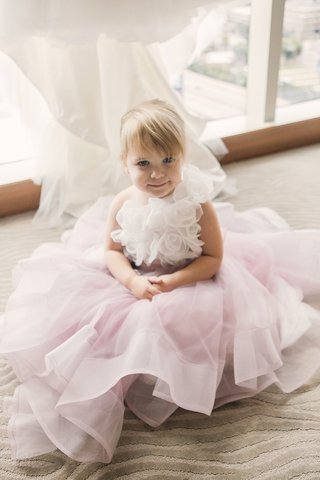 little-blonde-flower-girl-sitting-on-carpet-with-white-fabric-floret-bodice-and-layered-pink-skirt