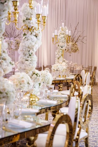 wedding-reception-s-shape-serpentine-table-tall-centerpiece-white-flowers-gold-candelabra-chairs