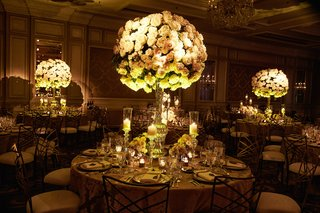 candlelight-ambient-wedding-reception-ballroom-tall-rounded-centerpiece-designs-of-roses-with-candle