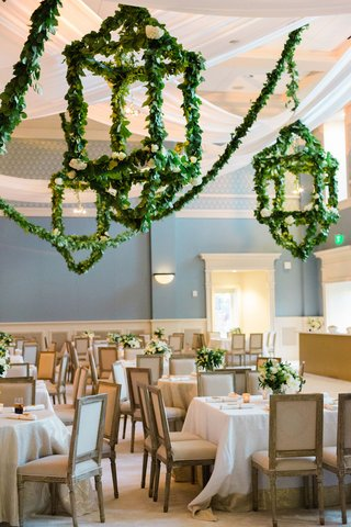 wedding-reception-greenery-garland-lanterns-overhead-square-tables-wood-chairs-white-flowers