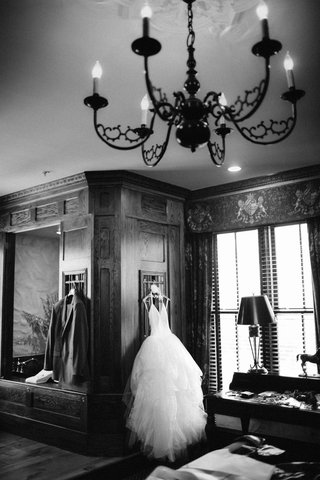 black-and-white-photo-of-brides-wedding-dress-and-grooms-tuxedo-jacket-hanging-near-each-other