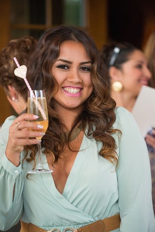 wedding-shower-guest-in-mint-dress-brown-belt-with-champagne-flute-pink-white-straw-gold-heart