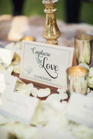 escort-card-table-with-white-rose-petals-gold-mercury-glass-vessel-instagram-wedding-hashtag-card
