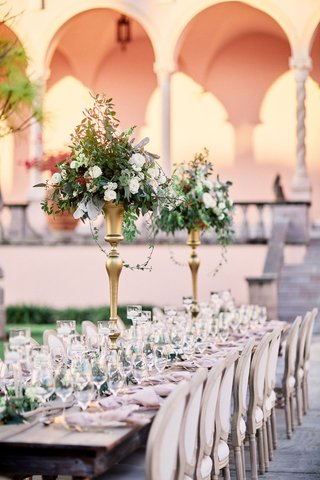 ringling-museum-outdoor-wedding-reception-long-tables-with-gold-stands-with-greenery-centerpieces