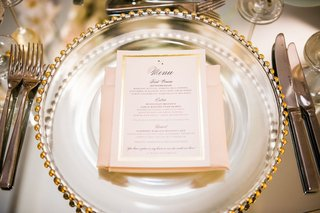 gold-foil-border-wedding-menu-card-on-gold-beaded-charger-plate-blush-napkin-calligraphy
