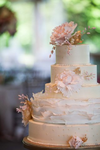 delicate-five-tier-white-wedding-cake-with-pink-flowers-and-gold-detailing-ruffles