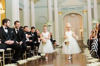 two-flower-girls-walk-down-the-aisle-toss-flower-petals-as-guests-look-on-wood-floor-biltmore