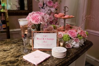 wedding-cocktail-hour-idea-hers-station-rose-and-champagne-bar-pink-flowers-macaron-desserts