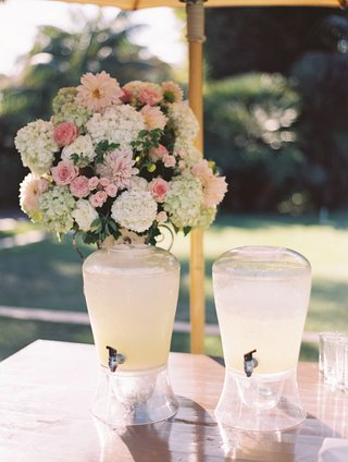 outdoor-wedding-ceremony-flower-arrangement-on-wood-table-with-drink-dispensers-filled-with-lemonade