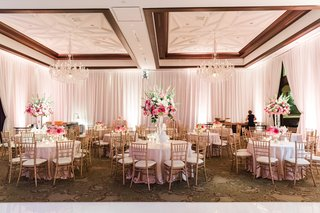 wedding-reception-with-gold-chiavari-chair-bright-pink-floral-centerpieces-chandeliers
