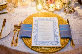 gold-ornate-charger-plate-and-gold-flatware-fork-knife-with-candles-and-light-blue-napkin-menu-card