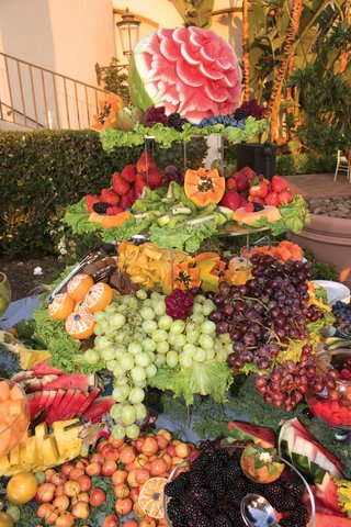 elaborate-and-luxurious-tower-of-fruit-with-cascading-grapes-and-carved-watermelon-at-cocktail-hour