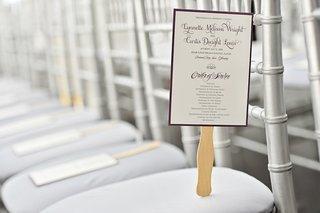 fan-wedding-ceremony-program-with-purple-border-script-on-silver-chair
