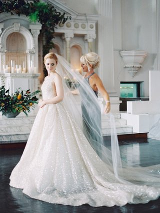 bride-in-sparkling-lazaro-wedding-dress-updo-long-veil-with-help-from-mother-of-bride-sleeveless