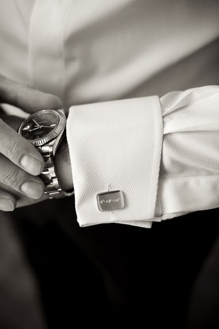 black-and-white-photo-of-grooms-engraved-cuff-links-and-watch-white-tuxedo-button-down-shirt