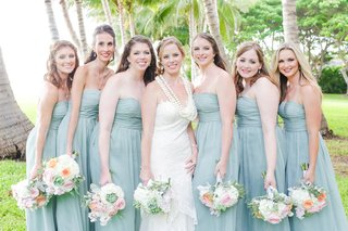 bridesmaids-in-sage-dresses-with-bride-in-white-bridal-gown-and-pastel-bouquets