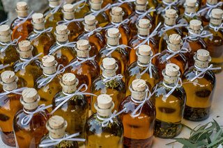 farm-wedding-reception-diy-favors-of-herb-olive-oil-in-corked-glass-bottles-white-ribbons