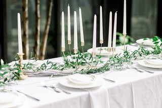 unique-curved-gold-candelabra-with-white-candles-and-greenery