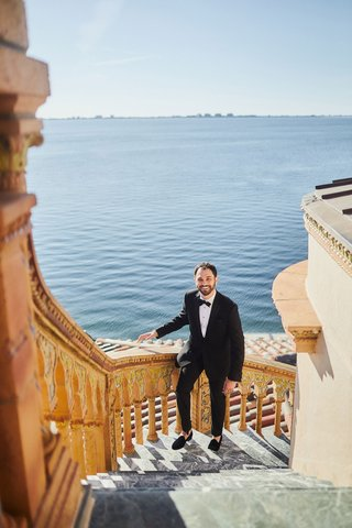 groom-in-tuxedo-and-slippers-walking-up-steps-of-ca-dvan-mansion