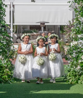 three-flower-girls-in-white-dresses-flower-crowns-carrying-white-greenery-pomander-bouquets-outdoor
