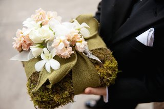 ring-bearer-holds-moss-ring-pillow-with-green-burlap-and-white-pink-flowers