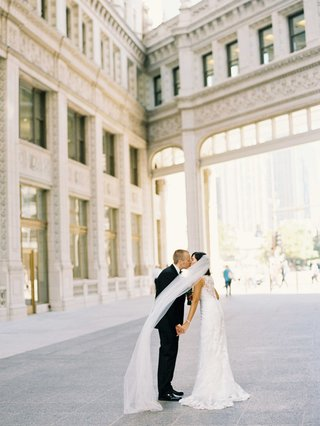 bride-in-lace-wedding-dress-with-long-veil-kisses-groom-in-chicago-courtyard-tuxedo-bow-tie