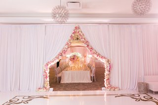 curtain-parted-and-lined-with-pink-and-white-flowers-separating-rooms-of-wedding-reception