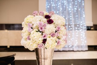 white-hydrangea-and-purple-rose-flower-arrangement-in-silver-vase-at-wedding-ceremony-string-lights
