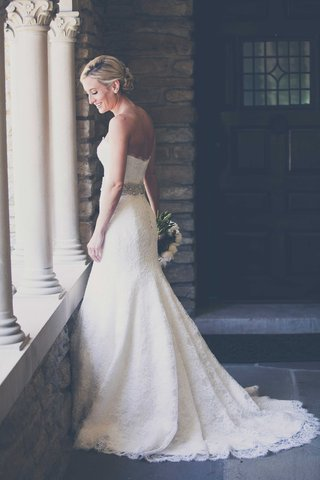 a-beautiful-bride-smiles-and-stares-down-at-ledge-in-her-monique-lhuillier-wedding-gown