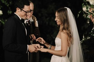 bride-at-wedding-ceremony-veil-long-hair-groom-putting-on-ring-with-glasses