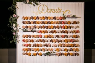 wedding-reception-desserts-favors-donut-wall-on-sticks-pegs-shiplap-pink-flowers-greenery