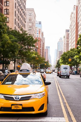 driver-in-a-yellow-toyota-new-york-city-taxi-waves-on-downtown-street