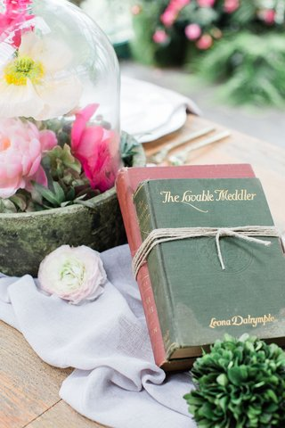 two-vintage-books-tied-with-twine-as-centerpiece-on-wedding-reception-table