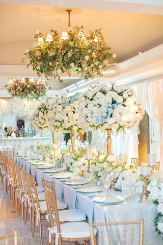 head-table-with-ivory-flower-runner-tall-arrangements-of-roses-and-chandeliers-with-greenery