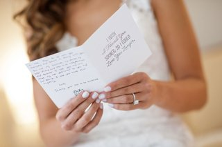 bride-with-white-manicure-reading-love-letter-card-from-groom-on-wedding-day