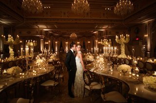 wedding-reception-at-the-mar-a-lago-club-formal-bride-and-groom-serpentine-tables-candles-white