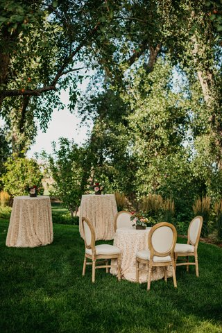 wedding-reception-garden-setting-cocktail-table-small-bistro-table-with-french-upholstered-chairs