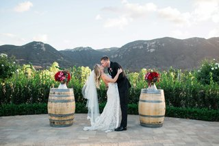 bride-and-groom-kiss-outside-on-vineyard-alfresco-barrels-red-and-purple-flowers-california