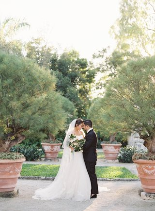 bride-in-wedding-dress-and-veil-touching-foreheads-of-groom-in-tuxedo-natural-bouquet-greenery