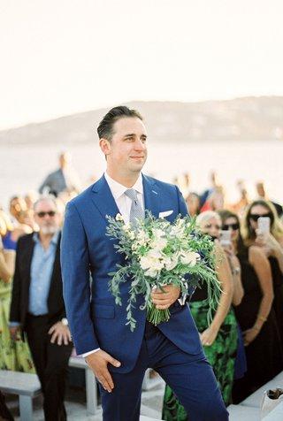 wedding-ceremony-greek-wedding-mykonos-groom-in-blue-suit-holding-bridal-bouquet-greenery-flowers