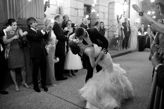 black-and-white-photo-of-bride-in-mermaid-dress-strapless-kisses-groom-during-sparkler-exit