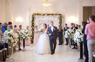 bride-in-wedding-dress-groom-in-grey-suit-linking-arms-flower-arch-fireplace-mirror-risers
