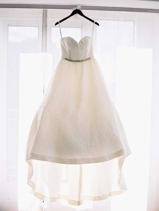 wedding-dress-hanging-up-in-window-strapless-sweetheart-neckline-ballgown-with-train