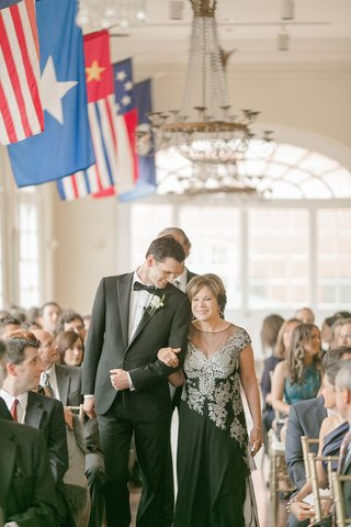 groom-in-black-tuxedo-walks-up-aisle-with-his-mother-in-a-black-illusion-neckline-dress-white-lace