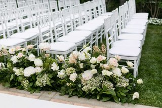 white-wedding-ceremony-chairs-on-grass-lawn-for-outdoor-nuptials-green-leaves-pink-white-roses
