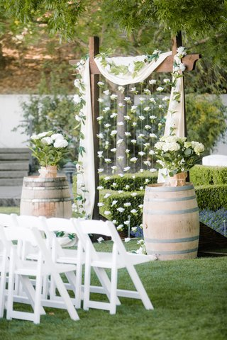 outdoor-wedding-ceremony-with-wooden-arch-strings-of-gardenias-and-potted-hydrangeas-on-barrels