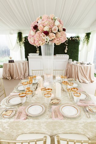 wedding-reception-hedge-wall-square-table-gold-plates-glassware-pink-napkins-centerpiece-damask